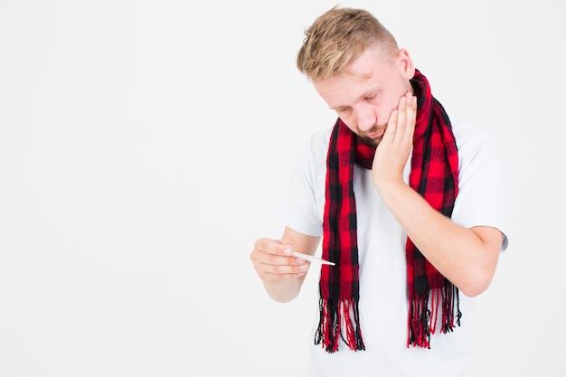 Homme tenant un thermomètre à la main