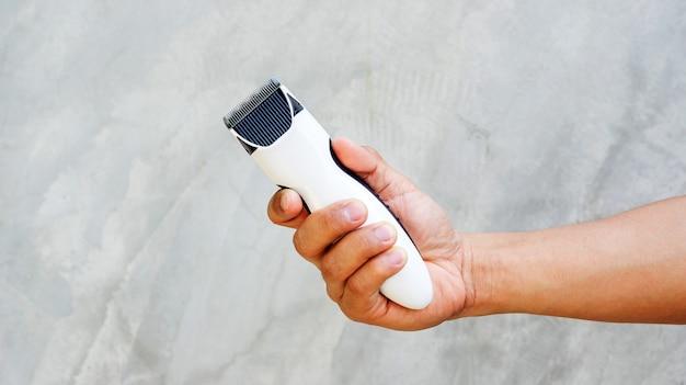Homme tenant une tondeuse à cheveux sans fil dans sa main.
