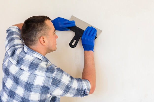 Homme tenant une truelle tout en travaillant sur le mur