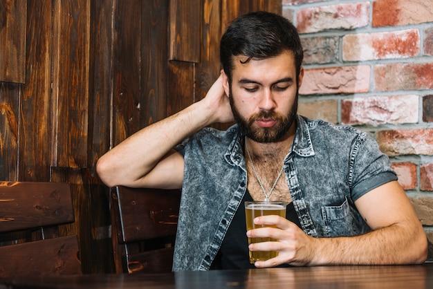 Homme tenant un verre de bière au bar