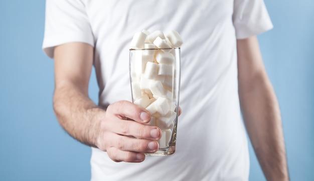 Homme tenant un verre avec des cubes de sucre.