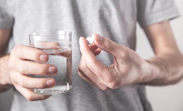 Homme tenant un verre d'eau et une tablette.