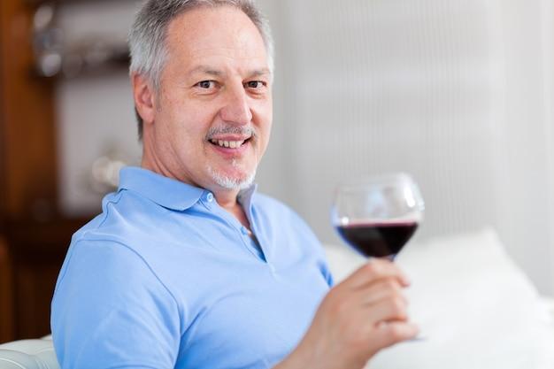 Homme tenant un verre de vin rouge