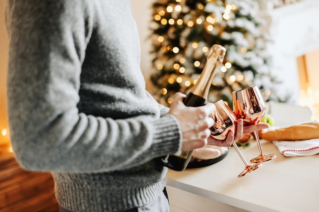 Homme tenant des verres à vin et champaigne