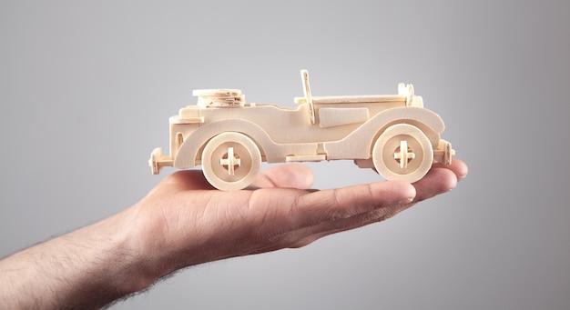 Homme tenant une vieille voiture jouet rétro en bois