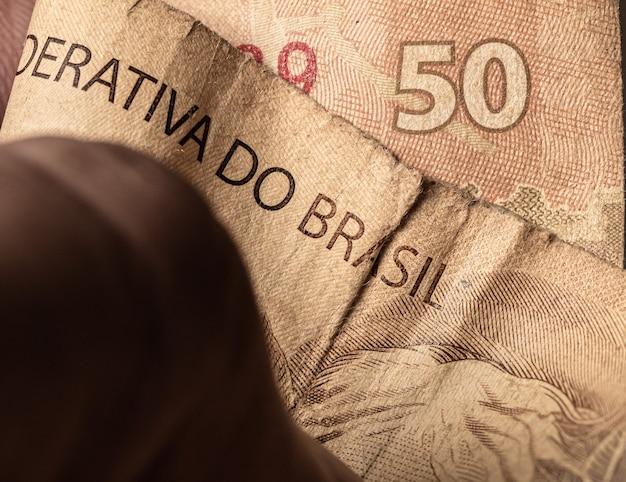 Un homme tenant un vrai projet de loi brésilien très utilisé et sale pour un concept sur l'économie brésilienne