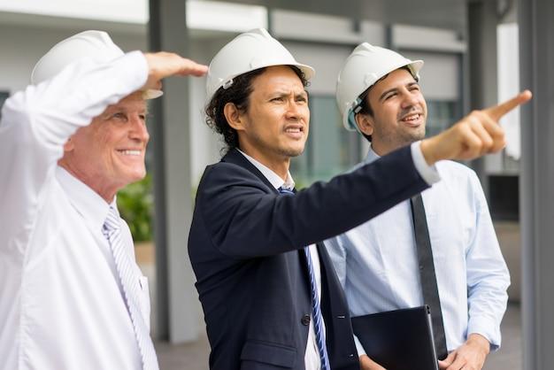 Homme tendu d'âge moyen en casque et costume pointant sur les bâtiments voisins