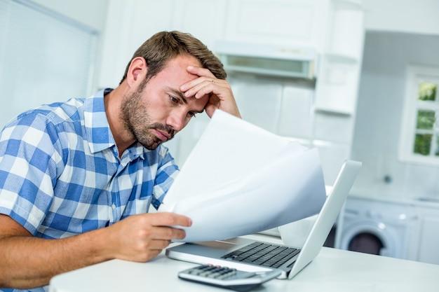Homme tendu à la recherche de documents tout en étant assis par ordinateur portable à table