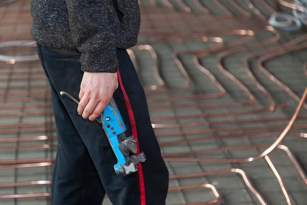 Homme tenir cintreuse pour tuyaux en cuivre