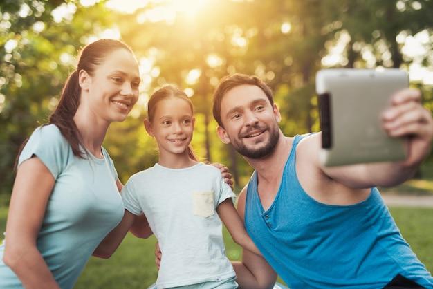 Homme tenir la tablette grise. la famille sportive donne selfie.