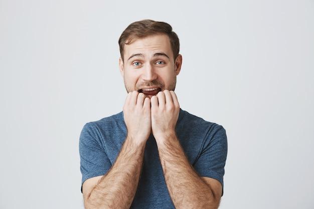 Homme tentant d'essayer le produit, se rongeant les ongles du désir