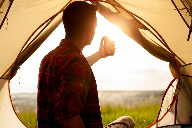 Homme en tente de camping prenant selfie