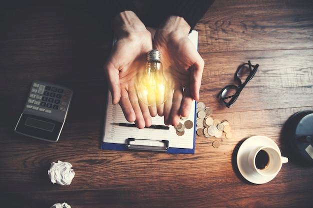 Homme, tenue, ampoule, papeterie, table