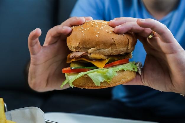 Homme, tenue, boeuf, burger, laitue, fromage, tomate, concombre, oeuf, vue côté