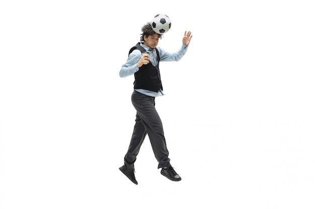 Homme en tenue de bureau jouant au football ou au football avec ballon sur espace blanc. look inhabituel pour homme d'affaires en mouvement, action. sport, mode de vie sain.