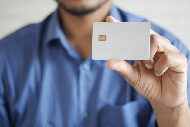 Homme en tenue décontractée montrant une carte de crédit