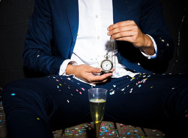 Homme en tenue de dîner, montre de poche près du verre entre les confettis