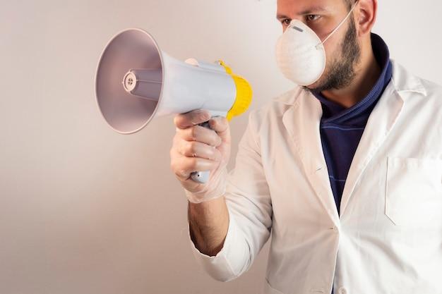 Homme en tenue de médecin avec un mégaphone