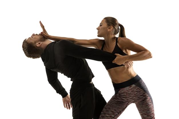 Homme en tenue noire et femme caucasienne athlétique combats sur fond de studio blanc. autodéfense des femmes, droits, concept d'égalité. faire face à la violence domestique ou au vol dans la rue.