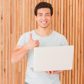 Homme, tenue, ordinateur portable, pouces, haut, geste