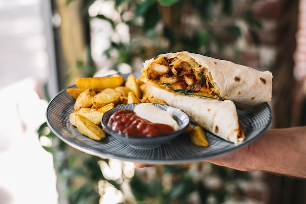 Homme, tenue, poulet, burrito, servi, frites, mayonnaise, ketchup