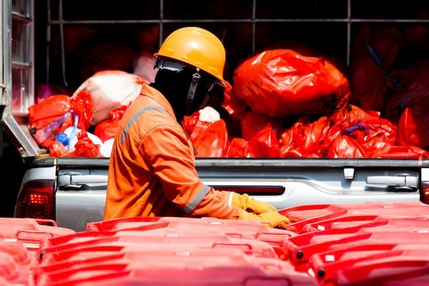 Homme en tenue de protection avec bac rouge d'infection et sac de déchets d'infection.