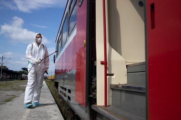 Homme en tenue de protection blanche désinfectant et désinfectant l'extérieur de la rame de métro pour arrêter la propagation du virus corona très contagieux