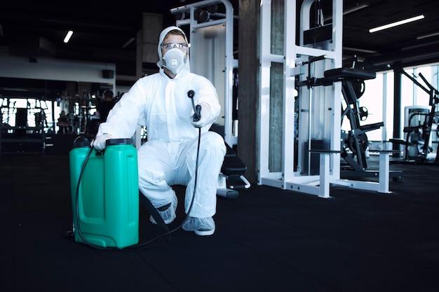 Homme en tenue de protection blanche désinfectant et équipement de fitness et poids pour arrêter la propagation du virus corona très contagieux