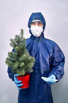 Homme en tenue de protection et masque avec un arbre de noël dans une main et des masques dans l'autre main.