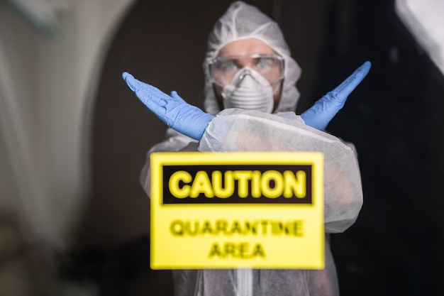 Homme en tenue de protection et masque médical de protection montrant le geste d'arrêt. l'épidémiologiste montre le geste non