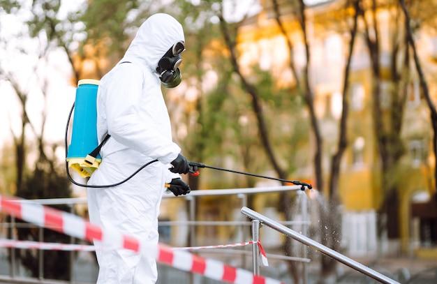 Un homme en tenue de protection et un masque pulvérise un désinfectant sur la balustrade dans le lieu public vide à l'aube dans la ville de quarantaine. covid 19. concept de nettoyage.