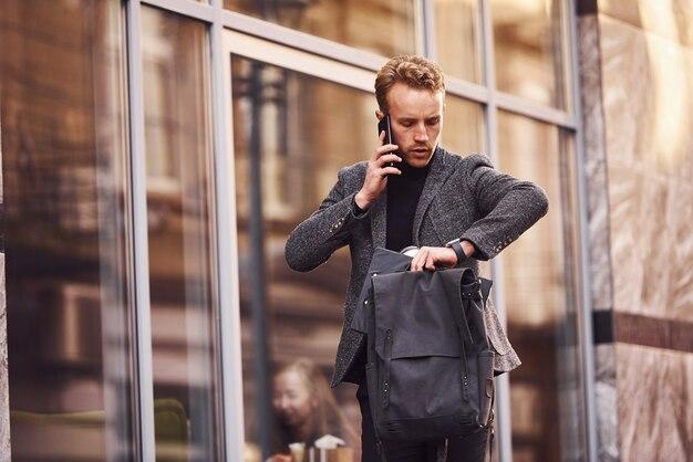 Homme en tenue de soirée élégante à l'extérieur contre un bâtiment moderne parlant par téléphone.