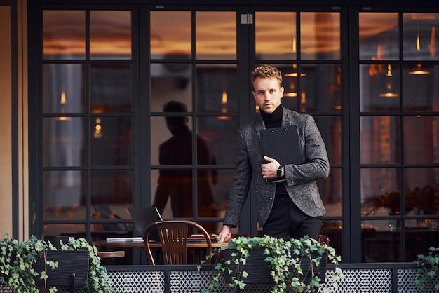 Homme en tenue de soirée élégante à l'extérieur contre un bâtiment moderne.