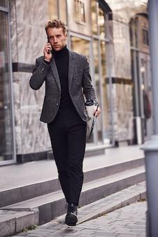 Un homme en tenue de soirée élégante avec une tasse de boisson et un bloc-notes dans les mains est à l'extérieur contre un bâtiment moderne et a une conversation par téléphone.