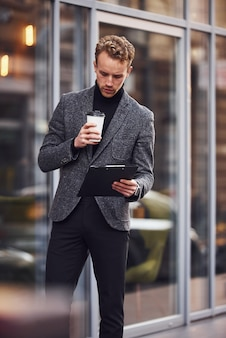 L'homme en tenue de soirée élégante avec une tasse de boisson et un bloc-notes dans les mains est à l'extérieur contre un bâtiment moderne.
