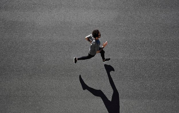 Homme en tenue de sport en cours d'exécution sur route