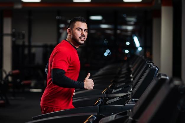 Homme en tenue de sport en cours d'exécution sur tapis roulant à la gym en vêtements rouges