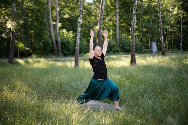 L'homme en tenue de sport se tient dans un asana pratiquant le yoga à l'extérieur sur l'herbe verte. journée internationale du yoga