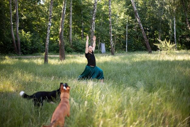 L'homme en tenue de sport se tient dans un asana pratiquant le yoga à l'extérieur sur l'herbe verte avec ses chiens