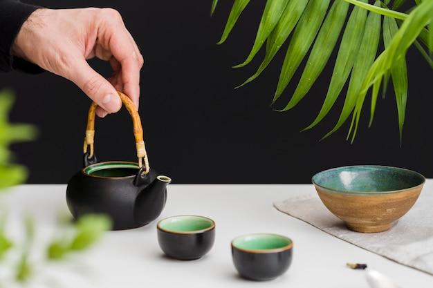 Homme, tenue, tasse thé, table