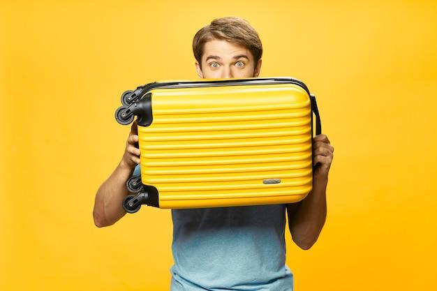 Homme, tenue, valise, passager, voyage, aéroport, fond jaune