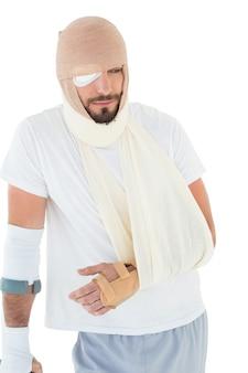 Homme avec la tête ligotée dans le bandage et la main cassée