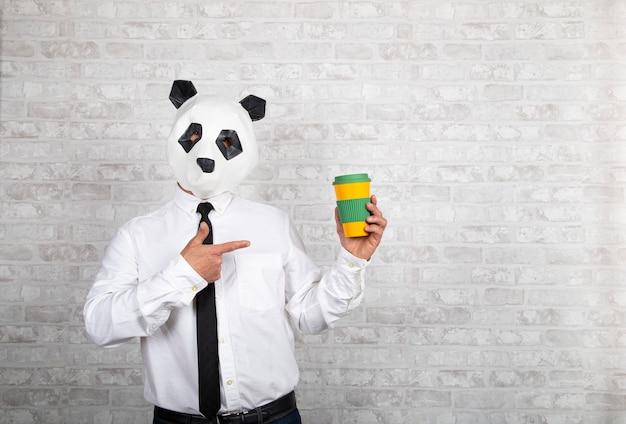Homme avec tête d'ours panda pointe vers une tasse de café à emporter