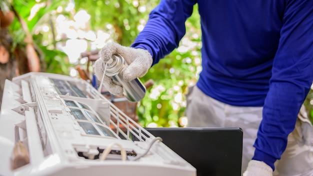 Un homme thaïlandais apprend en ligne et répare le climatiseur à la maison. nouvelle vie normale après covid-19. verrouillage et auto-quarantaine. restez à la maison et distanciation sociale.