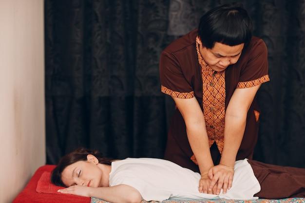 Homme thaïlandais faisant procédure de massage thaï classique à la jeune femme au salon de beauté spa