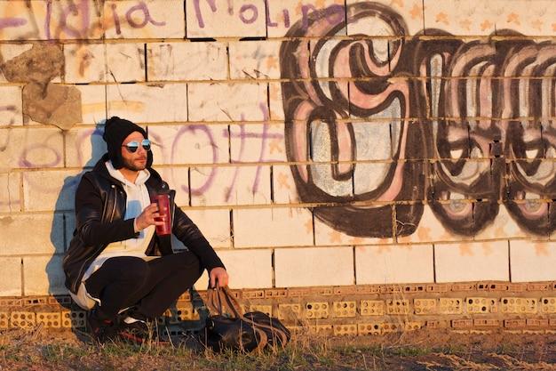Homme avec thermos près du mur