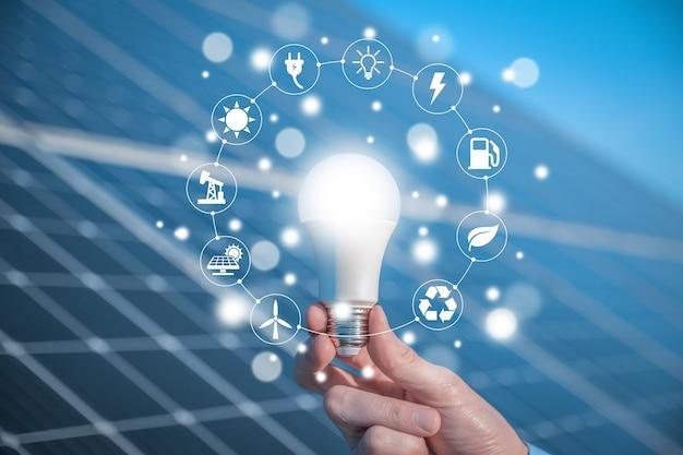 L'homme tient une ampoule, une ampoule led de panneaux solaires avec des icônes sources d'énergie pour un développement renouvelable et durable. concept d'écologie.