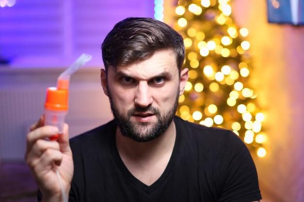 L'homme tient un appareil d'inhalation pulmonaire dans le contexte des lumières de noël