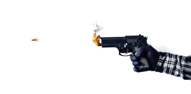 L'homme tient une arme à feu avec une balle qui en sort. isolé sur fond blanc.