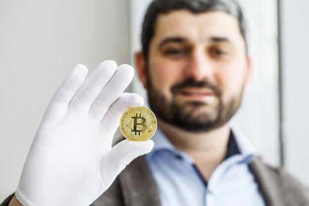 L'homme tient des bitcoins dans son bureau